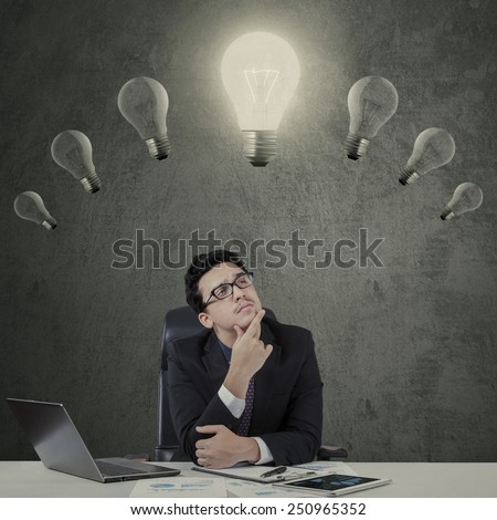 Businessperson working on desk while looking at the illuminated light bulb over his head - stock photo