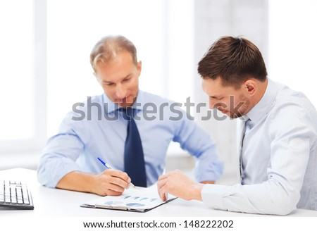 businesss concept - two businessmen discussing graphs on meeting - stock photo