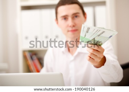 businesss man with Euro money sitting in office - stock photo