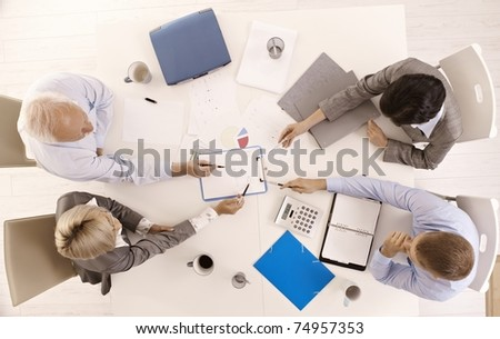 Businessteam busy working at meeting table, pointing at document, overhead view.? - stock photo
