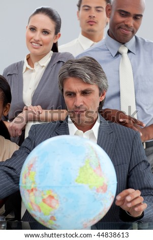 Businessteam looking the earth and imagine travel - stock photo