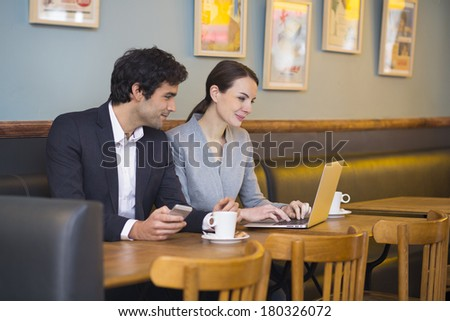 Businessteam working on laptop at coffee bar - stock photo