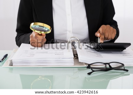 Businesswoman Analyzing Bills With Magnifying Glass On Desk - stock photo