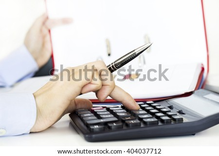 Businesswoman analyzing graphic and using calculator in the office