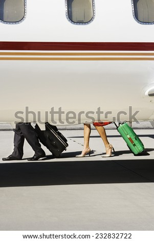 Businesswoman and Businessman Alighting From Private Jet - stock photo