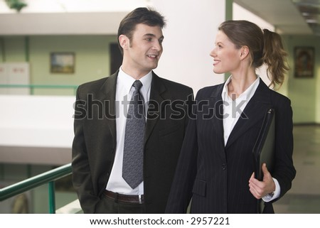 Businesswoman and businessman are walking and talking