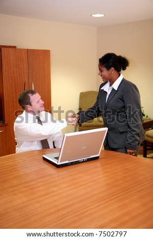 Businesswoman and Businessman looking at a computer