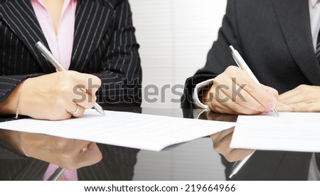businesswoman and businessman signing document after coordination