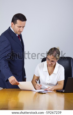 businesswoman and businessman signing papers in the office