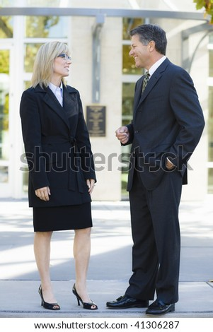 Businesswoman and Businessman Standing Outdoors Looking at Each Other