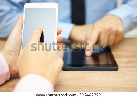 Businesswoman and businessman using smart mobile phone and digital tablet computer for computing and communication - stock photo