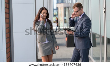 Businesswoman and businessman working outside with mobile phone and tablet pc.