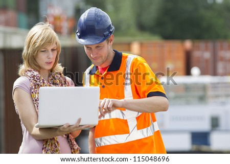 Businesswoman and construction worker discussing new project on laptop - stock photo