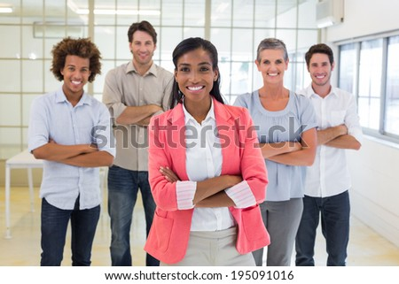 Businesswoman and coworkers smiling at camera in the office - stock photo