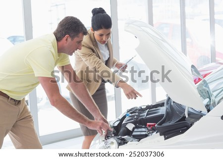 Businesswoman and customer looking at a car engine at new car showroom - stock photo