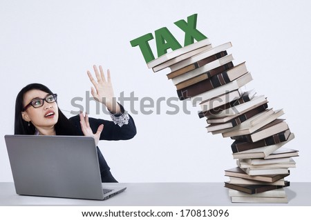Businesswoman and falling tax from stack of books - stock photo