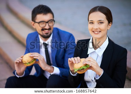 Businesswoman and her colleague eating sandwiches outside - stock photo