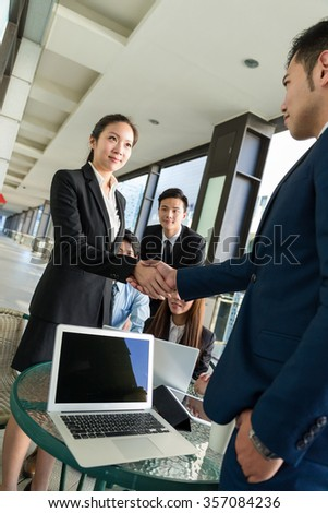 Businesswoman and man shaking hand for making a deal
