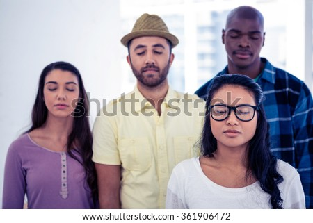Businesswoman and team with eyes closed in creative office - stock photo