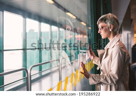 Businesswoman at airport looking at window. - stock photo