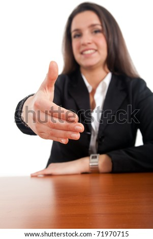 Businesswoman at her desk lending a hand for a welcome handshake - stock photo