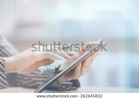 Businesswoman at office working with digital PC beinhd the window - stock photo