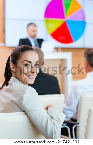 Businesswoman at the conference. Confident young woman in formalwear looking over shoulder and smiling while sitting at the conference hall with public speaker in the background - stock photo