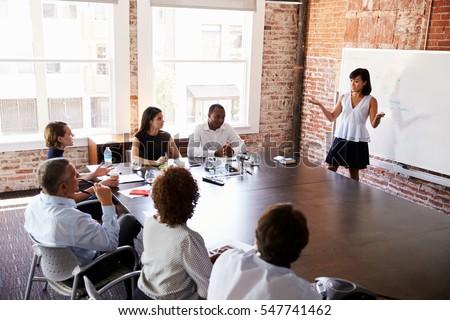 businesswoman whiteboard giving presentation boardroom stock photo