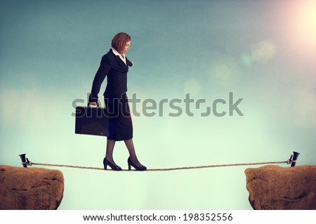 businesswoman balancing on a tightrope conquering adversity concept - stock photo