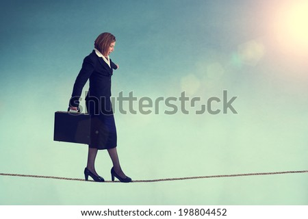 businesswoman balancing on a tightrope or highwire - stock photo