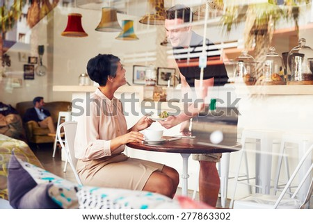 Businesswoman being served by waiter in a coffee shop - stock photo
