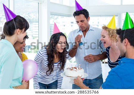 Businesswoman blowing candles on her birthday cake in the office - stock photo