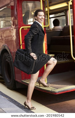 Businesswoman boarding Routemaster bus - stock photo