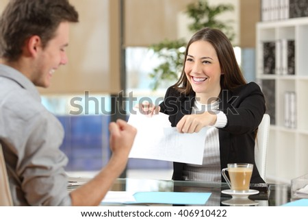 Businesswoman breaking contract with a happy client at office - stock photo