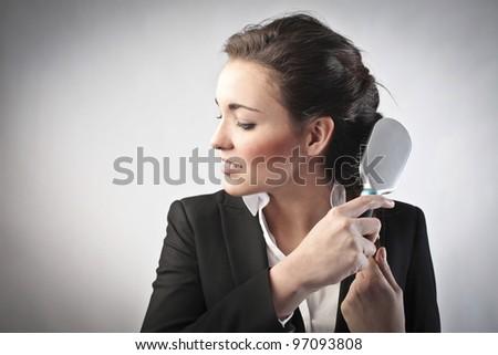 Businesswoman brushing her hair - stock photo
