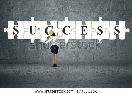 Businesswoman builds or completes a big puzzle - stock photo