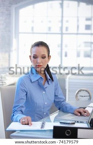 Businesswoman busy working at office desk reviewing documents and using laptop computer.? - stock photo