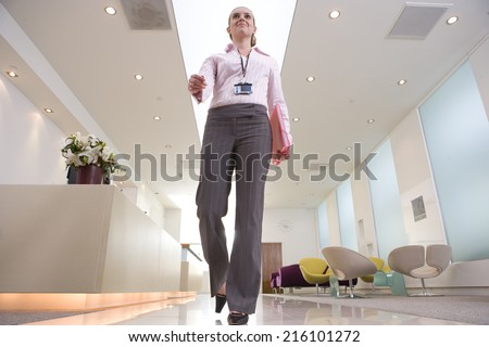 Businesswoman by reception, low angle view - stock photo