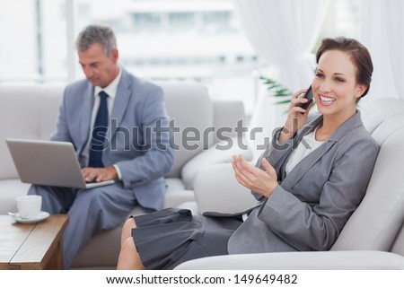 Businesswoman calling while her colleague working on his laptop in bright office - stock photo