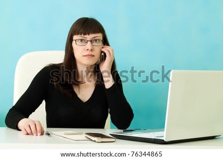 Businesswoman calls phone sitting on table in office - stock photo