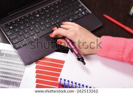 businesswoman checking budget or payroll with laptop - stock photo
