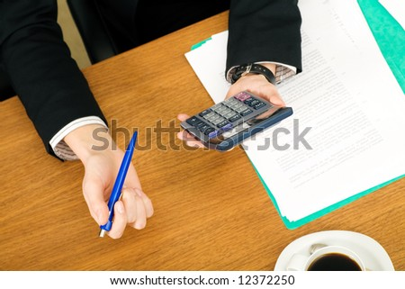 Businesswoman checking the numbers using a calculator - stock photo