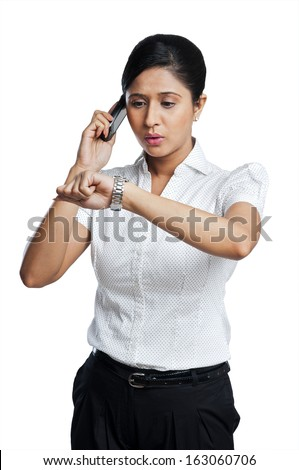 Businesswoman checking the time while talking on a mobile phone - stock photo