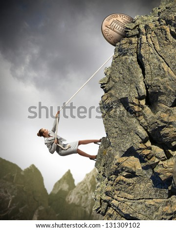 businesswoman climbing mountain with cent on top - stock photo