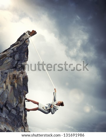 businesswoman climbing steep mountain hanging on rope - stock photo