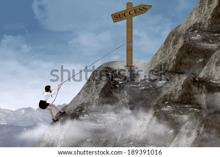 Businesswoman climbing steep mountain with success sign on top