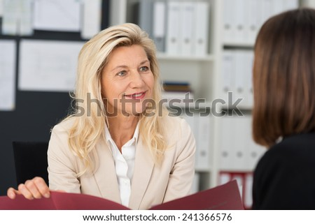 Businesswoman conducting a job interview holding the female applicants CV in her hands as she questions her in the office