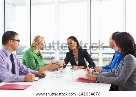 Businesswoman Conducting Meeting In Boardroom - stock photo