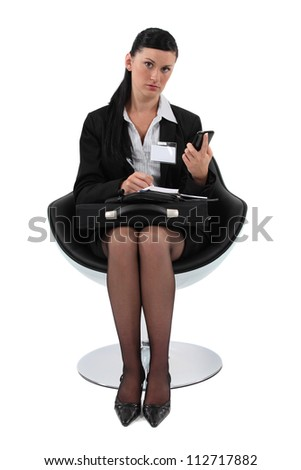 Businesswoman copying a telephone number into her agenda - stock photo
