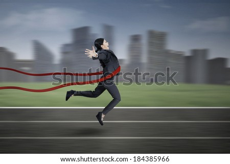 Businesswoman crossing the finish line with cityscape background - stock photo